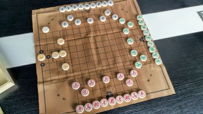 Unlike the previous two three-player variants of Chinese Chess/象棋/Xiangqi, this version is fully professional (and has a decently long history).  The board is professionally printed, the pieces custom made for the set, and the rules, instead of being a bunch of JPG images (first game) or little strips of paper that look like they were printed on a POS terminal (second game), are printed professionally on proper print stock with colour ink.  Of course you pay for what you get.  This game has almost no changes to piece movement, but as with the first game lacks the key strategy of pinning opposition.  It also has four sides, despite there being only three players.  The yellow pieces to the left are the fourth side and they begin the game aloof.  They do nothing (and can have nothing done to them) until a piece of any of the other teams reaches the black spots around the yellow general.  The specific spot landed on determines who is now allied with the yellow pieces--whoever that is adds the yellow pieces to their own forces--while the other two team up to fight against them.  The yellow pieces are VERY powerful (three chariots and a cannon), so don't let the low piece count fool you.  As with the first game, it's hard to use cannon pins.  As with the second game, the middle part adds a dimension to the board, in this case a sizable dimension (9x9 grid) which changes some key movement and placement strategies.